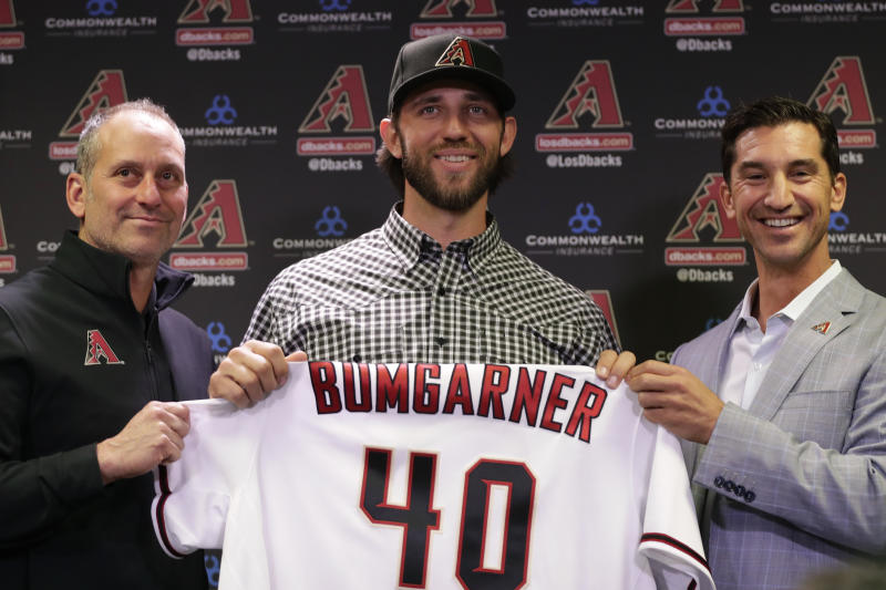Newly acquired Arizona Diamondbacks pitcher Madison Bumgarner, center, holds his new jersey with general manager Mike Hazen, right, and manager Tory Lovullo during a team availability, Tuesday, Dec. 17, 2019, in Phoenix. (AP Photo/Matt York)