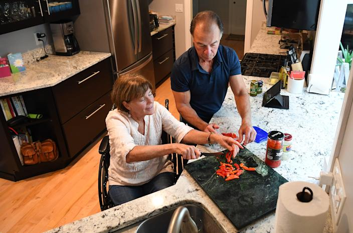 Nancy Poon, who has ALS, is shown in her Rhode Island kitchen with husband Alan Poon.