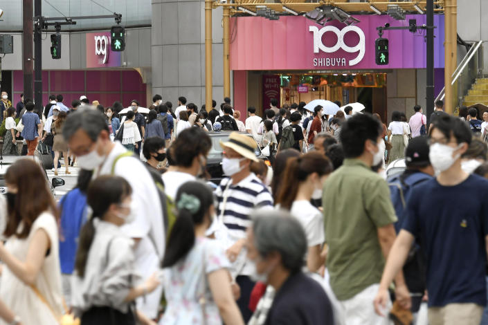 People wearing face masks make their way at an intersection in Tokyo Saturday, Aug. 7, 2021. Tokyo reported more than 4,500 coronavirus cases on Saturday. (Kyodo News via AP)