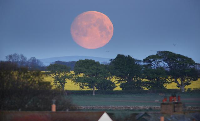 The moon sets over a house in Bamburgh, Northumberland, on Wednesday morning, ahead of the final supermoon of the year. (PA)