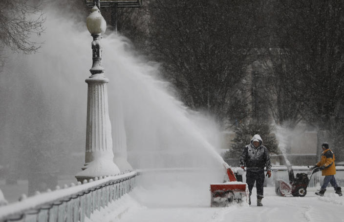 Men clears the snow inside the skating rink in Millennium Park, after a snow storm in Chicago Saturday Jan. 19, 2019. ( Abel Uribe/Chicago Tribune via AP)
