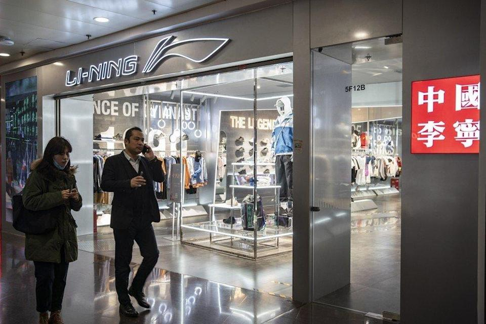Li Ning is among the three stocks to be added to the Hang Seng Index next month. Pedestrians walk past a Li-Ning Sports Goods Co. store in Shanghai, China, March 2021. Photo: Bloomberg