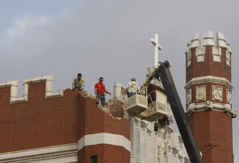 FILE - Maintenance workers inspect the damage to one of the spires on Benedictine Hall at St. Gregory's University in Shawnee, Okla. on Sunday, Nov. 6, 2011. Two earthquakes in the area in less than 24 hours caused one of the towers to topple, and damaged the remaining three. A team of scientists have determined that a 5.6 magnitude quake in Oklahoma in 2011 was caused when oil drilling waste was injected deep underground. The report was released Tuesday, March 26, 2013 by the journal Geology. That makes it the most powerful quake to be blamed on deep injections of wastewater, although not everyone agrees. Oklahoma's state seismologists say the quake was natural. (AP Photo/Sue Ogrocki)