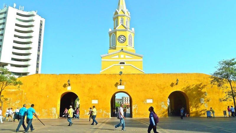 A picture of the the city gate of Cartagena de Indias in Columbia, with a bright yellow wall and a spire rising over it.