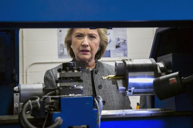 Then-U.S. presidential candidate and former Secretary of State Hillary Clinton inspects a robot CNC machine while touring the New Hampshire Technical Institute Community College in Concord, New Hampshire, April 21, 2015. REUTERS/Lucas Jackson