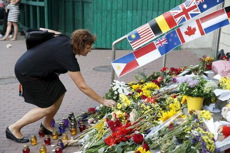 A woman places flowers outside the Dutch embassy to commemorate the victims of the Malaysia Airlines flight MH17 plane crash a year ago in Kiev, Ukraine, July 17, 2015. REUTERS/Valentyn Ogirenko