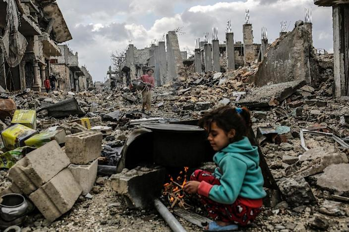 Kurdish Syrian girls are pictured among destroyed buildings in the heavily shelled Syrian Kurdish town of Kobane on March 22, 2015 (AFP Photo/Yasin Akgul)