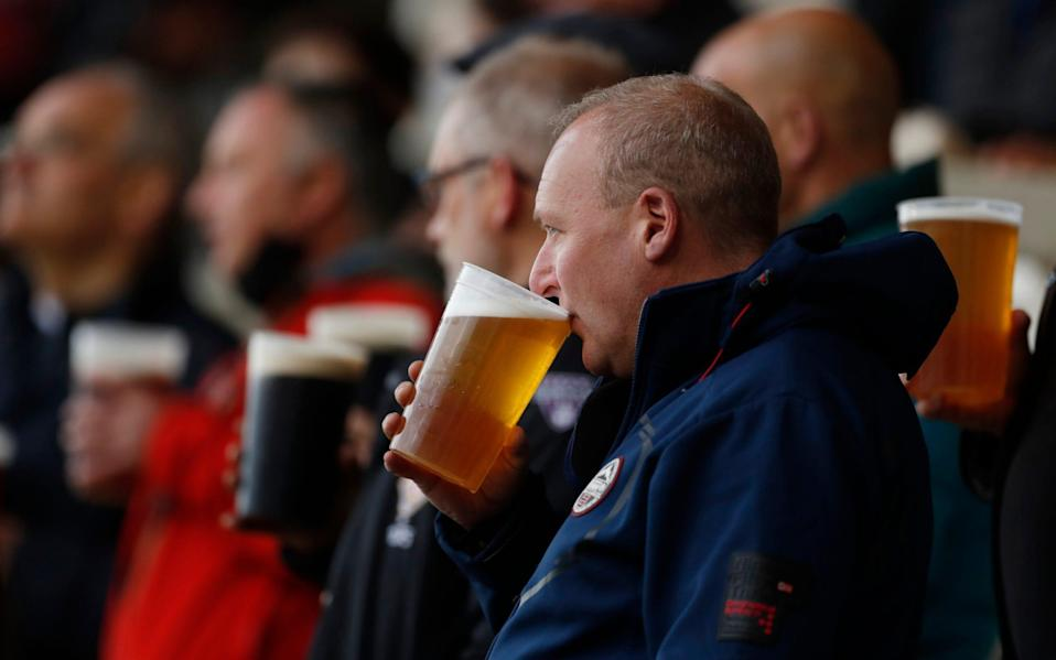 Fans drinking beer inside the stadium before the match as a limited number of fans are permitted at outdoor sports venues - Action Images via Reuters/Lee Smith