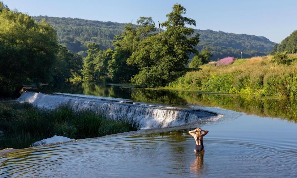 A swimmer standing in the shallows of the River Avon at Warleigh Weir in Somerset, England.