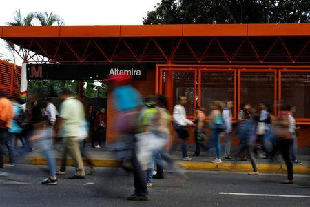 People walk in front of a closed metro station during a blackout in Caracas, Venezuela February 6, 2018. REUTERS/Carlos Garcia Rawlins