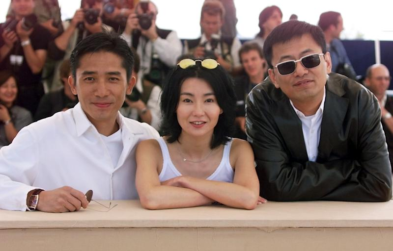 Chinese actors Maggie Cheung and Tony Leung (C) pose during the photocall of director Wong Kar-Wai's (R) movie 'In the Mood for Love', during the Cannes Film Festival, in 2000 (AFP Photo/Jack Guez)
