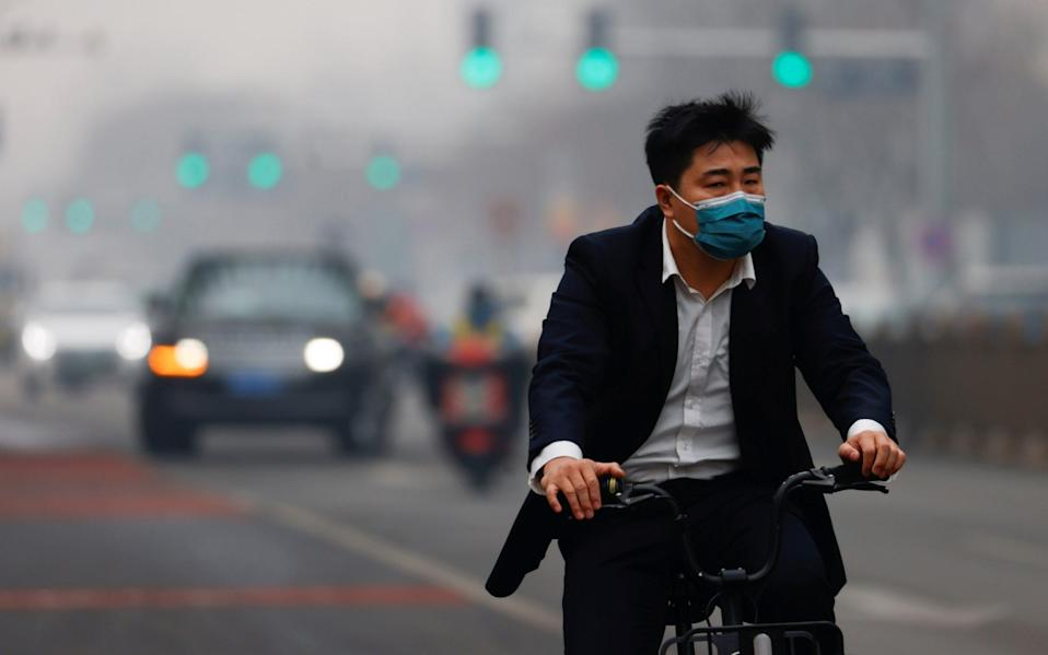 A man wearing face mask rides a bicycle on the street on Saturday