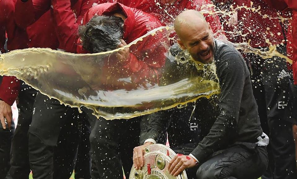 Bayern Munich head coach Pep Guardiola is doused in beer by Bayern Munich's David Alaba (L) as they celebrate their Bundesliga title (AFP Photo/Christof Stache)