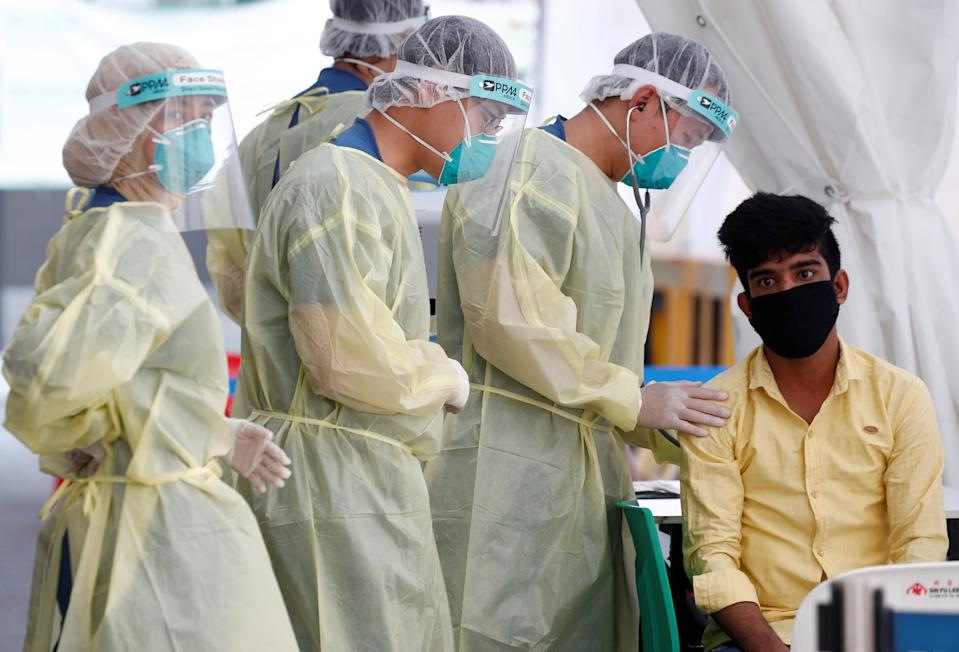 Medical workers prepare to perform a nose swab on a migrant worker at a dormitory, amid the coronavirus disease (COVID-19) outbreak in Singapore May 15, 2020.  REUTERS/Edgar Su