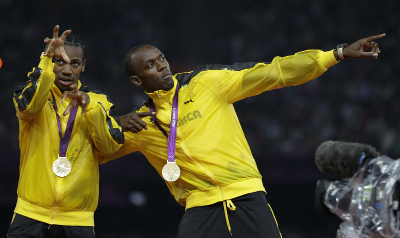 Jamaica's Usain Bolt and Yohan Blake celebrate as they receive their gold medals for the men's 4x100-meter during the athletics in the Olympic Stadium at the 2012 Summer Olympics, London, Saturday, Aug. 11, 2012. (AP Photo/Matt Slocum)