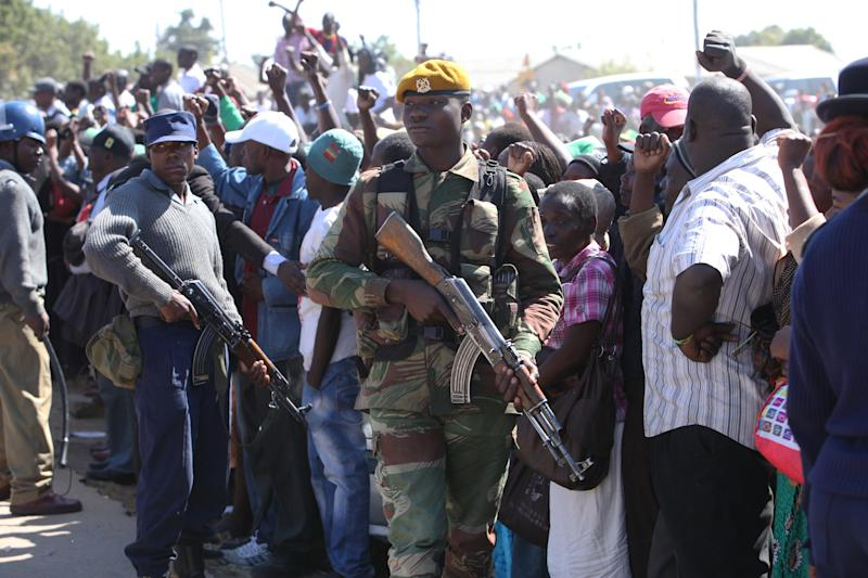 An armed soldier stands guard at President Robert Mugabe's campaign rally in Chitungiwiza, Zimbabwe, about 20 kilometers south of Harare, Tuesday, July 16, 2013. Zimbabwe is set to hold Presidential elections on July 31, 2013. (AP Photo/Tsvangirayi Mukwazhi)