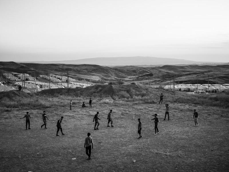 Refugees play soccer inside the Bardarash camp, which had hosted Iraqis displaced by the offensive against ISIS in Mosul and reopened in October to accommodate Kurds fleeing the Turkish offensive in Syria. | Moises Saman—Magnum Photos for TIME