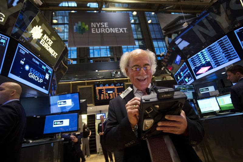 A trader smiles as he works on the floor of the New York Stock Exchange after the market opening in New York