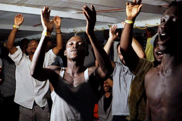 PHOTO: Migrants on board the Open Arms vessel celebrate the news of an Italian prosecutor who has ordered that the migrants be disembarked on the island of Lampedusa, southern Italy, Aug. 20, 2019. (Francisco Gentico/AP)