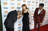 """Ismael Kanater, left, a cast member in """"The Forgiven,"""" kisses the hand of cast member Jessica Chastain, center, as cast member Mourad Zaoui looks on at the premiere of the film at the 2021 Toronto International Film Festival, Saturday, Sept. 11, 2021, in Toronto. (AP Photo/Chris Pizzello)"""