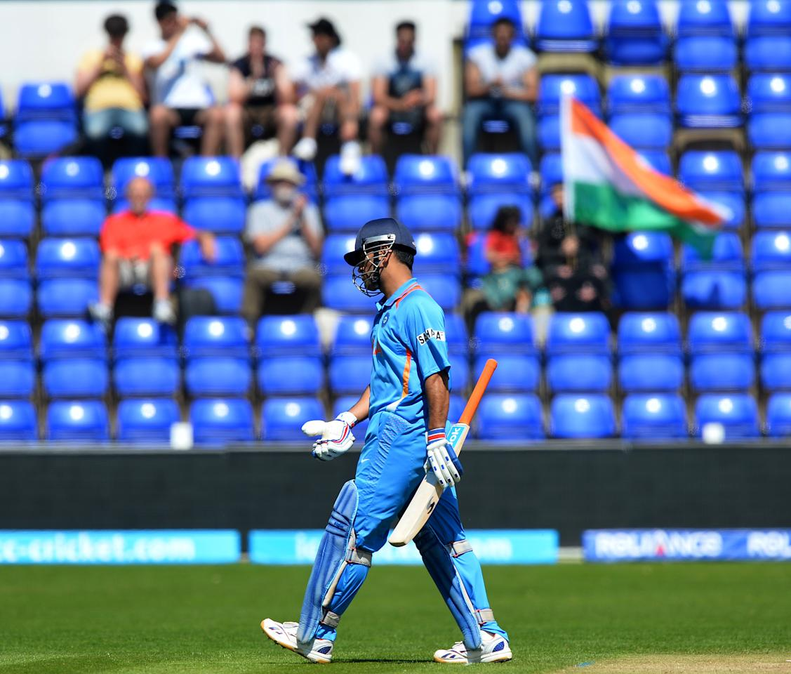 India's captain Mahendra Singh Dhoni leaves the pitch following his dismissal during the warm-up cricket match ahead of the 2013 ICC Champions Trophy between India and Australia at The Cardiff Wales Stadium in Cardiff, Wales on June 4, 2013.  India, having won the toss and elected to bat first, scored 308 runs for the loss of six wickets. AFP PHOTO/Paul Ellis        (Photo credit should read PAUL ELLIS/AFP/Getty Images)
