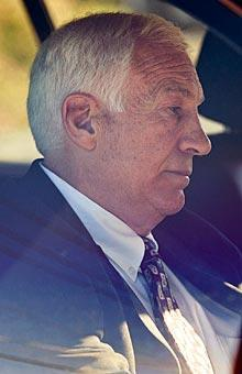 Jerry Sandusky sits in a car as he leaves the office of Centre County Magisterial District Judge Leslie A. Dutchcot on Saturday