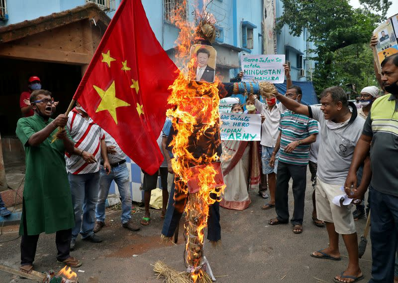 FILE PHOTO: Demonstrators shout slogans as they burn an effigy depicting Chinese President Xi Jinping during a protest against China, in Kolkata