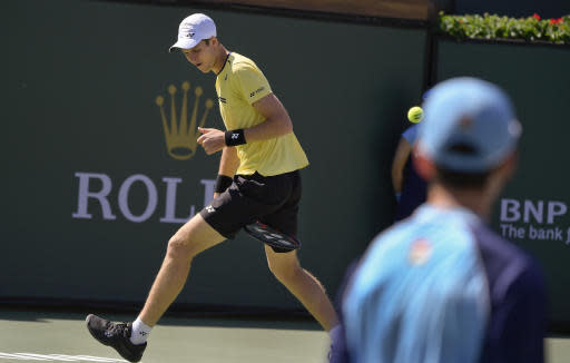 Hubert Hurkacz, of Poland, hits a shot between his legs to Roger Federer, of Switzerland, at the BNP Paribas Open tennis tournament Friday, March 15, 2019, in Indian Wells, Calif. (AP Photo/Mark J. Terrill)