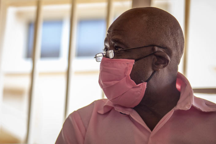 """Paul Rusesabagina, whose story inspired the film """"Hotel Rwanda"""", wears a pink prison uniform as he appears for a bail hearing at a court in the capital Kigali, Rwanda Friday, Sept. 25, 2020. Rusesabagina admitted in court that he helped to form the National Liberation Front rebel group in order to assist Rwandan refugees, but denied that he supported any violence or killings. (AP Photo/Muhizi Olivier)"""