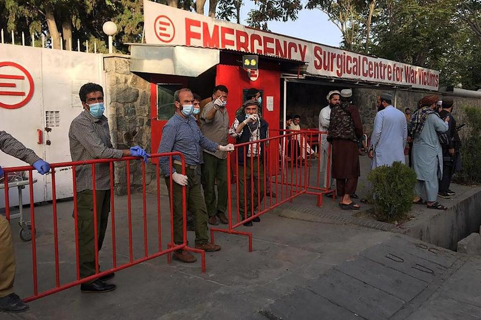 Afghan medical staff members stand at the entrance of a hospital as they wait to receive the victims of an explosion in Kabul  (AFP via Getty Images)