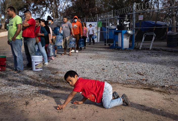Asylum-seekers stand in line to receive fresh water distributed at a migrant camp at the U.S.-Mexico border on February 23, 2021, in Matamoros, Mexico. / Credit: Getty Images