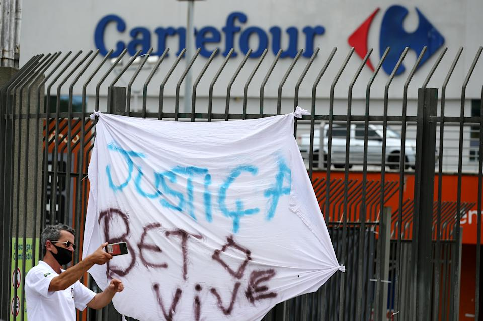 "A man takes a picture next to a banner that's reads: ""Justice. Beto lives"", after Joao Alberto Silveira Freitas was beaten to death by security guards at a Carrefour supermarket in Poro Alegre, Brazil, November 20, 2020. REUTERS/Diego Vara"