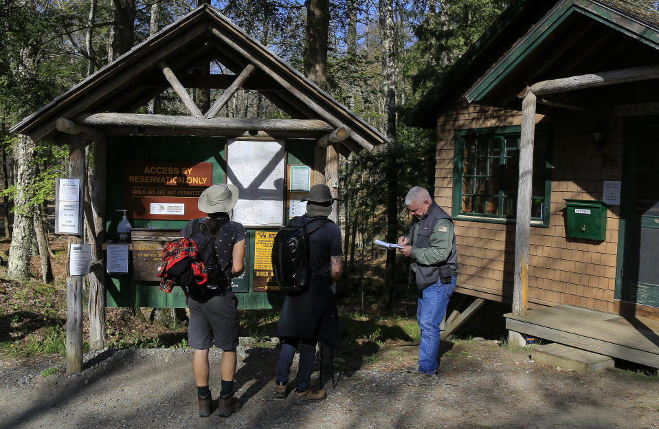 Adirondack Mountain Reserve Ranger Mike Ryan, right, checks in two hikers at the trailhead of the reserve, Saturday, May 15, 202, in St. Huberts, N.Y. A free reservation system went online recently to control the growing number of visitors packing the parking lot and tramping on the trails through the private land of the Adirondack Mountain Reserve. The increasingly common requirements, in effect from Maui to Maine, offer a trade-off to visitors, sacrificing spontaneity and ease of access for benefits like guaranteed parking spots and more elbow room in the woods. (AP Photo/Julie Jacobson)