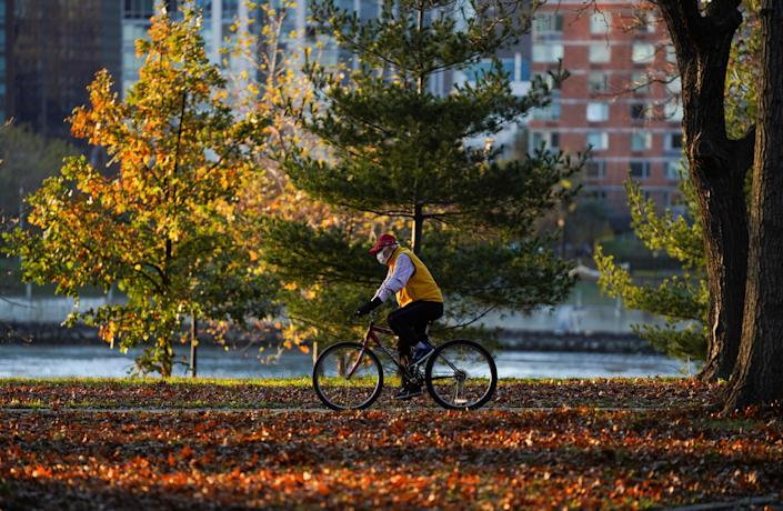 (201115) -- NEW YORK, Nov. 15, 2020 (Xinhua) -- A man wearing a face mask rides at a park in New York, the United States, Nov. 14, 2020.   The United States has reported more than 10.8 million COVID-19 cases in total with the death toll from the disease exceeding 245,000 as of Saturday afternoon, showed a tally by Johns Hopkins University. (Xinhua/Wang Ying) (Xinhua/Wang Ying via Getty Images)