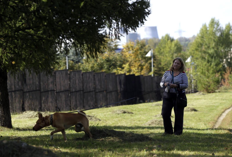 In this Thursday Sept. 20, 2012 photo Olga Krasotova walks her ddog in a park, where dozens of dogs were killed in a mass poisoning of dogs, in Moscow. On Friday, Sept. 21, 2012, police opened a criminal probe into the suspected poisoning of animals by dog killers, the latest such incident in Russia where cruelty to animals is common and animal protection laws are rarely enforced. This well-heeled neighborhood has always cherished its enormous park, where they could give their dog a moment's respite from cramped city living and let them frolic without a leash in the grass or in the snow. (AP Photo/Sergey Ponomarev)