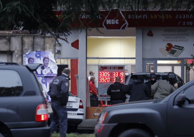 Law enforcement officers gather in a street near an office of a microfinance organisation after an unidentified gunman took hostages, in Tbilisi