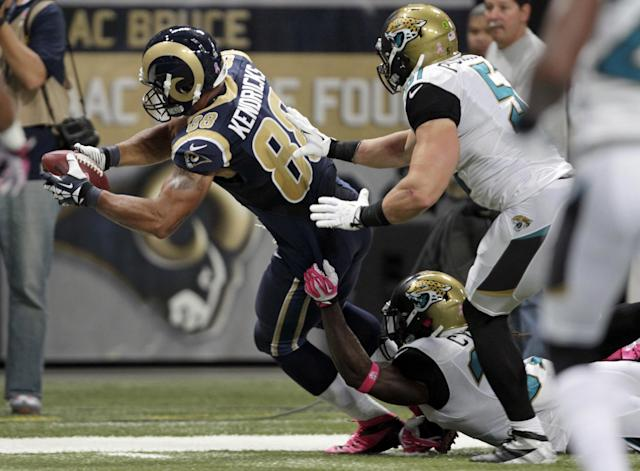 FILE - In this Oct. 6, 2013, file photo, St. Louis Rams tight end Lance Kendricks, left, dives past Jacksonville Jaguars defenders John Cyprien, bottom, and Paul Posluszny, right, after catching a 16-yard pass for a touchdown during the second quarter of an NFL football game in St. Louis. This season, Kendricks has 20 catches for 159 yards and three touchdowns. Eleven of his receptions have been for first downs and he had a season-high five catches against Dallas. (AP Photo/Tom Gannam, File)