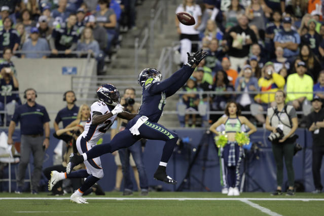 Seattle Seahawks wide receiver DK Metcalf reaches for an incomplete pass under pressure from Denver Broncos cornerback Isaac Yiadom, left, during the first half of an NFL football preseason game Thursday, Aug. 8, 2019, in Seattle. (AP Photo/Stephen Brashear)