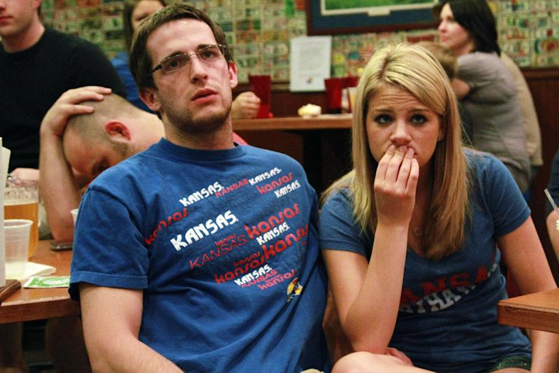 Kansas fans Andrew Murray, of Olathe, Kan., and his girlfriend Kasey Crostarosa watch a television broadcast of the NCAA Final Four tournament college basketball championship game between Kansas and Kentucky, Monday, April 2, 2012, at Jefferson's Restaurant in Lawrence, Kan. Kentucky won 67-59. (AP Photo/The Lawrence Journal-World, Richard Gwin)