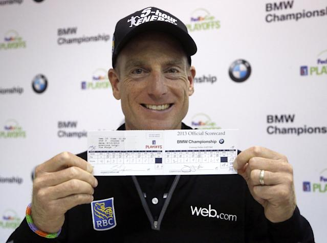 Jim Furyk holds up his scorecard after a news conference in the second round of the BMW Championship golf tournament at Conway Farms Golf Club in Lake Forest, Ill., Friday, Sept. 13, 2013. Furyk posted a single round 59, tying a PGA Tour record. (AP Photo/Charles Rex Arbogast)