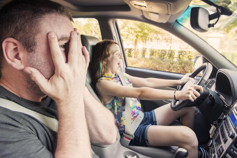 This is a horizontal color photograph of a young red-haired teenager learning to drive. She laughs recklessly in the background while her father covers his eyes in terror but cannot resist peeking through his fingers hoping that she doesn't crash and wreck the family vehicle.