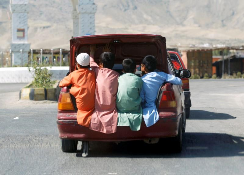 FILE PHOTO: Afghan boys travel in the back of a car during Eid al-Fitr, a Muslim festival marking the end the holy fasting month of Ramadan, amid the spread of the coronavirus disease (COVID-19), in Laghman province