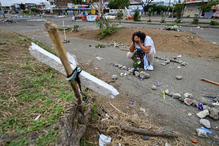 A woman cries at the grave of a protester killed during clashes between anti-government demonstrators and police in Cali