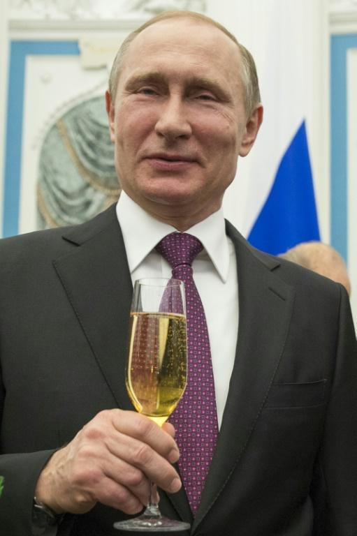 Russian President Vladimir Putin holds a glass of bubbly in 2016