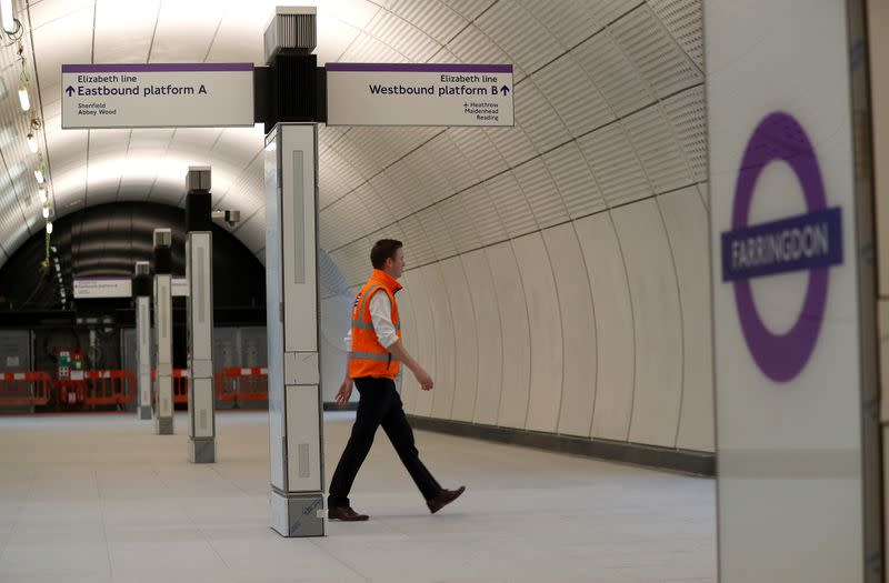 FILE PHOTO: A Crossrail employee walks in the new Farringdon underground station of the Elizabeth line which opens in December 2018, in London