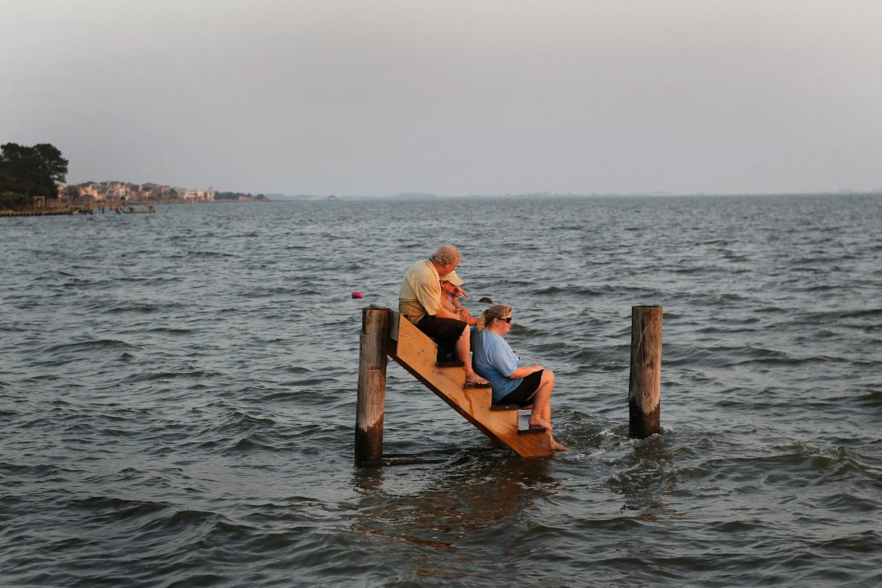 "NAGS HEAD, NC - AUGUST 28:  Billy Stinson (L), his wife Sandra Stinson (C) and daughter Erin Stinson comfort each other as they sit on the steps where their cottage once stood August 28, 2011 in Nags Head, North Carolina. The cottage, built in 1903 and destroyed yesterday by Hurricane Irene, was one of the first vacation cottages built on Albemarle Sound in Nags Head. Stinson has owned the home, which is listed in the National Register of Historic Places, since 1963. ""We were pretending, just for a moment, that the cottage was still behind us and we were just sitting there watching the sunset,"" said Erin afterward.  (Photo by Scott Olson/Getty Images)"
