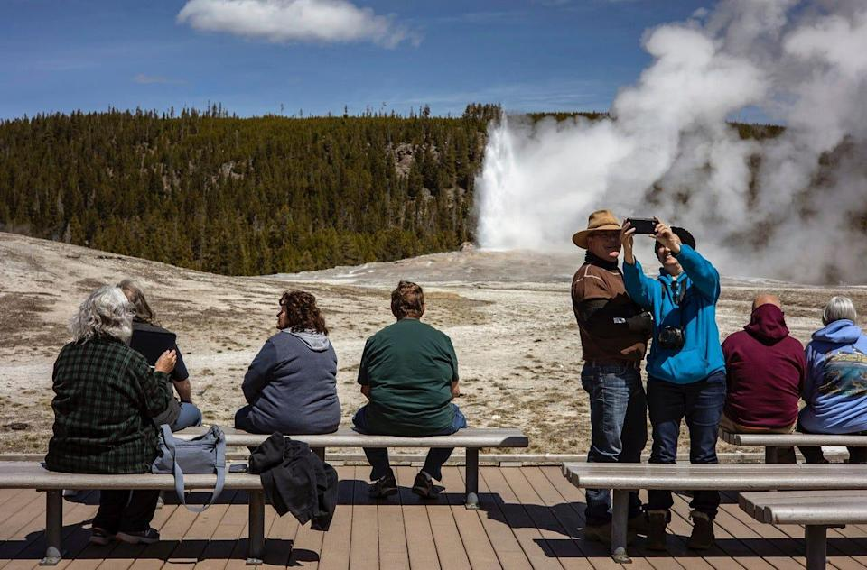 Tourists watch Old Faithful erupt at Yellowstone National Park in April, a month that saw record visitation to the park.