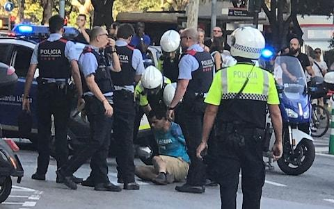 Police detain a possible suspect after the Barcelona attack - Credit: Jason Yu/Twitter