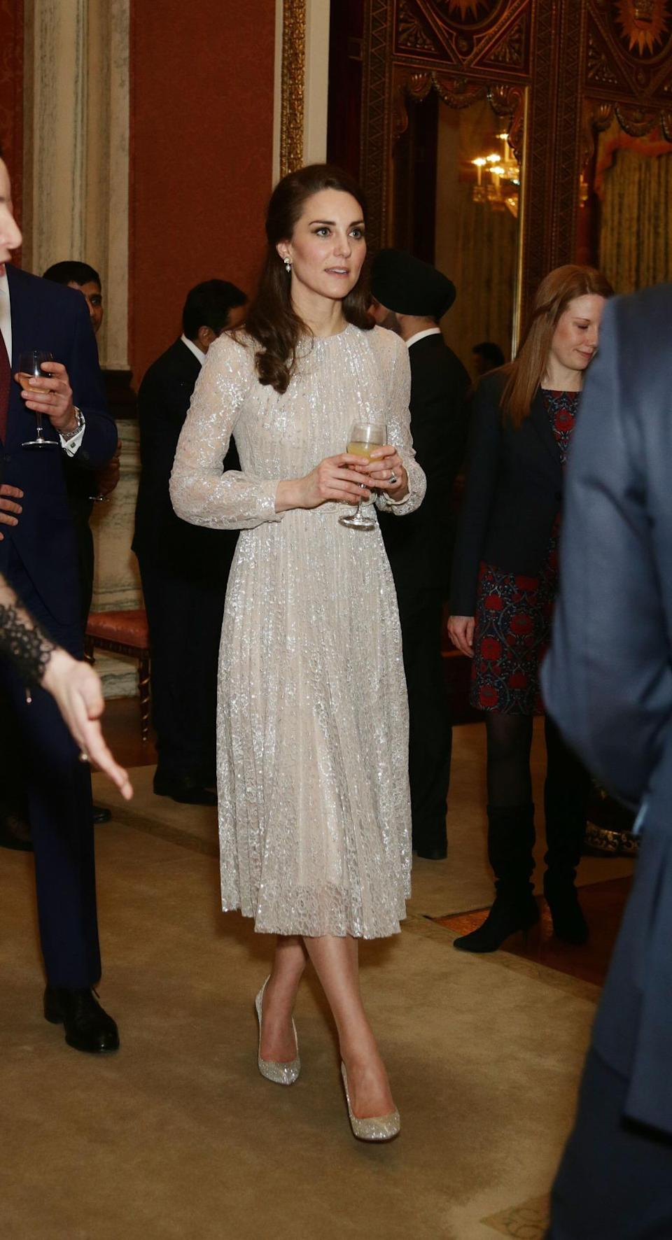 """<p>For a reception held at Buckingham Palace to celebrate the UK-India Year of Culture, Kate chose a look by her favourite British designer, Erdem. The cocktail dress was made from a metallic lace and featured semi-sheer sleeves as well as a pleated skirt. It sold out straight after the Duchess wore it but luckily, her glittering Oscar de la Renta heels can <a href=""""http://www.oscardelarenta.com/new-arrivals/platinum-lame-cabrina-pumps"""" rel=""""nofollow noopener"""" target=""""_blank"""" data-ylk=""""slk:still be yours"""" class=""""link rapid-noclick-resp"""">still be yours</a>. </p><p><i>[Photo: PA]</i> </p>"""