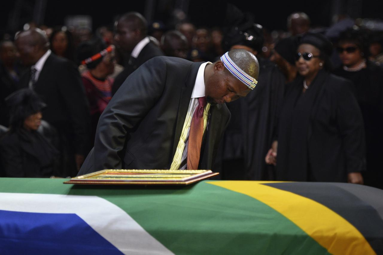Mandla Mandela, grandson of former South African President Nelson Mandela looks at the coffin of Nelson Mandela during his funeral ceremony in Qunu December 15, 2013. REUTERS/Odd Andersen/Pool (SOUTH AFRICA - Tags: SOCIETY OBITUARY POLITICS)
